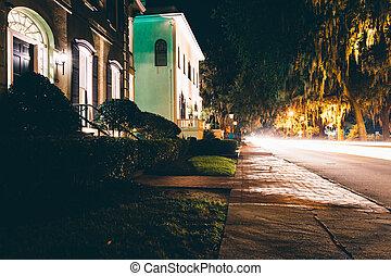 Casas y tráfico por la noche en la calle Drayton en Savannah, Georgia