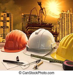 Casco de seguridad en arquitectos, ingenieros en mesas de trabajo con edificios modernos y construcción de grúas, uso de fondo para la construcción y la ingeniería civil, temas de bienes raíces