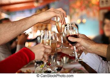 Celebración. Las manos sosteniendo las copas de champán y el vino haciendo un brindis.
