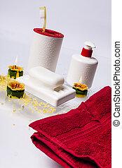 Cepillos de dientes, jabón, jabón líquido y toalla roja en fondo blanco.