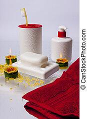 Cepillos, jabón, jabón líquido y toallas rojas en blanco.