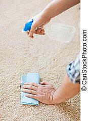 Cerca de la mancha de limpieza masculina en la alfombra