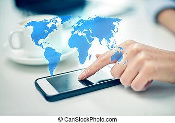 Cerca de la mano de la mujer con smartphone y mapa