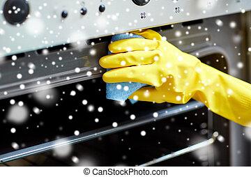 Cerca de mujeres limpiando el horno en la cocina