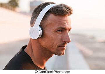 Cerca de un deportista confiado escuchando música