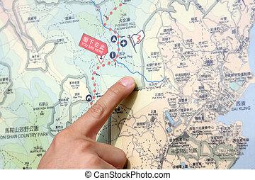 Cerca de una mano señalando la ubicación en el mapa.
