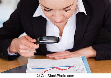 Cerca de una mujer mirando una carta con una lupa
