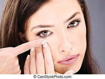 Cerca de una mujer poniéndole lentes de contacto en el ojo