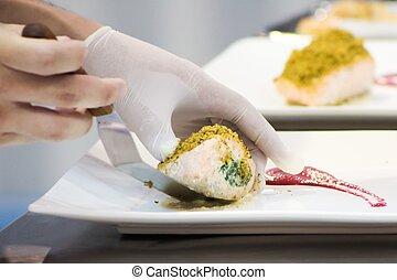 Cerca del chef decorando carne de salmón en el plato