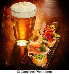 Cerveza fría con aperitivos gourmet