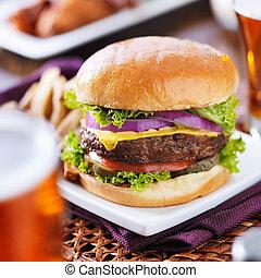 Cerveza y hamburguesa con alitas de pollo al fondo