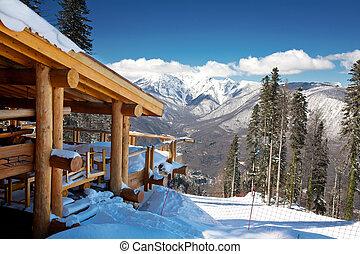 Chalet de esquí de madera en la nieve, en la montaña