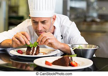 Chef de repostería masculino concentrado decorando postre en la cocina