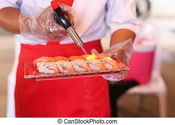 Chef de restaurante japonés asando sushi de salmón