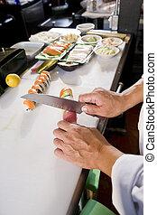 Chef en el restaurante japonés preparando rollitos de sushi