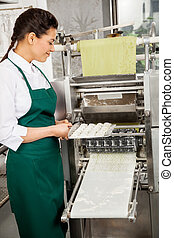 Chef hembra preparando pasta ravioli en la máquina