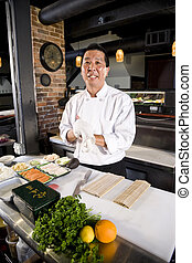 Chef japonés en el restaurante con ingredientes para el sushi
