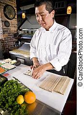 Chef japonés en el restaurante haciendo sushi