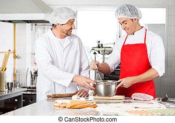 Chefs felices discutiendo mientras preparan pasta ravioli en la cocina