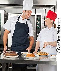Chefs felices preparando dulces platos en la cocina