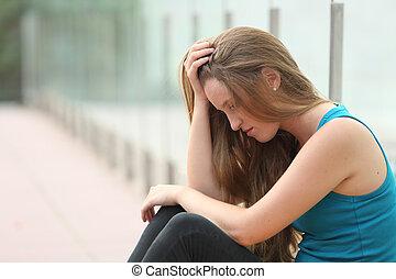 Chica adolescente sentada al aire libre deprimida