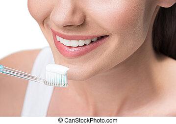 Chica alegre cuidando de su cavidad oral