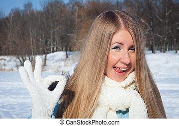Chica alegre muestra lengua en el parque. Una mañana helada en el parque