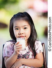 Chica asiática bebe leche