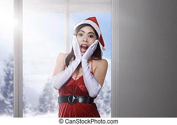Chica asiática con vestido de Santa con una expresión graciosa