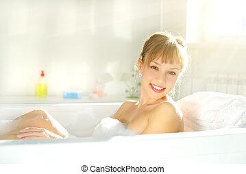 Chica atractiva relajándose en el baño