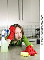 Chica cansada limpiando la cocina