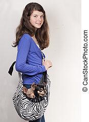 Chica con perro en una bolsa