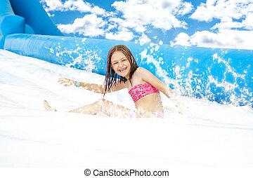 Chica deslizarse en el parque acuático