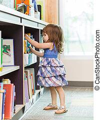 Chica eligiendo el libro de la biblioteca de la escuela