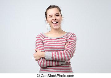 Chica estudiante guiñando el ojo mirando a la cámara con cara alegre riendo.