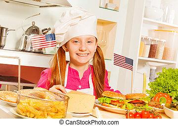 Chica feliz con uniforme de cocinero preparando comida americana
