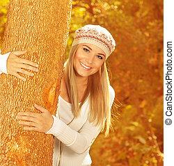 Chica feliz en el parque de otoño