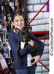Chica feliz llevando bulldog francés en la tienda