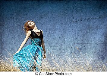 Chica pelirroja en el campo ventoso.