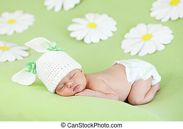 Chica recién nacida durmiendo en verde prado entre margaritas
