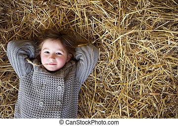 Chica relajada en heno y pensando