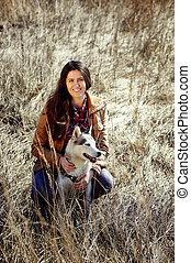 Chica sentada en el campo con fornido y sonrisas.
