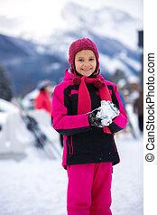 Chica sonriente con traje de esquí rosa haciendo bola de nieve