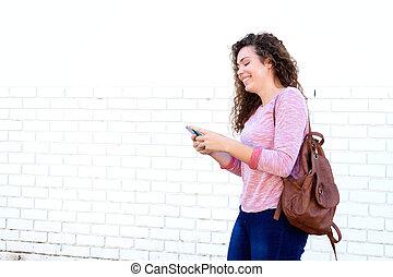 Chica sonriente parada y enviando mensajes con mochila