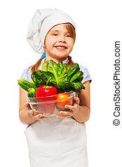 Chica sonriente sosteniendo un tazón lleno de vegetales frescos