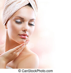 Chica Spa. Una hermosa joven después del baño tocándose la cara