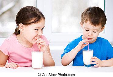 Chica y niño beben leche fresca