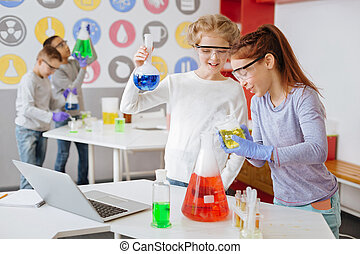 Chicas alegres comprobando la corrección de la reacción química