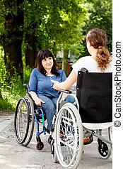 Chicas discapacitadas en sillas de ruedas durante la conversación