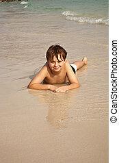 Chico, acostado en la playa y disfrutando del calor del agua y viéndose confiado y feliz